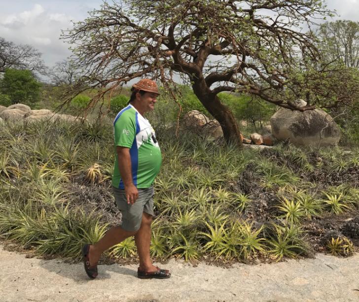 Jorge Leite, de alpercata xô boi e chapéu de vaqueiro, passeando perto de macambiras e de um pé de mulungu, na Lagoa do Pedrosa.