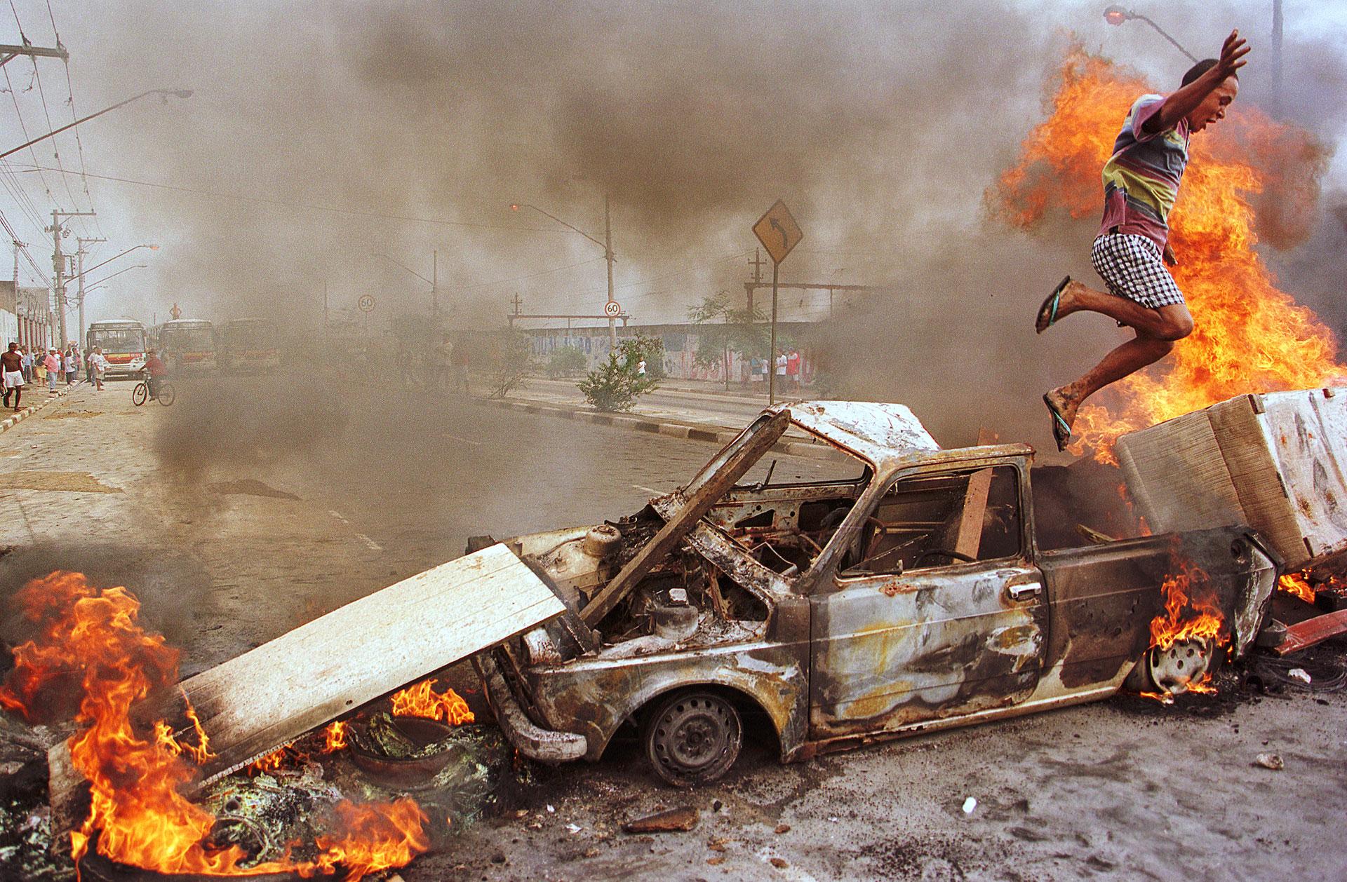 São Paulo, Brasil, 20 de março de 1998: depois de diversas enchentes, moradores de Ermelino Matarazzo, na periferia da cidade, queimaram veículos para pedir mais investimentos do governo para diminuir o problema dos alagamentos. Neste clique, um homem que colocou fogo em um carro se afasta da cena, advertido por um policial