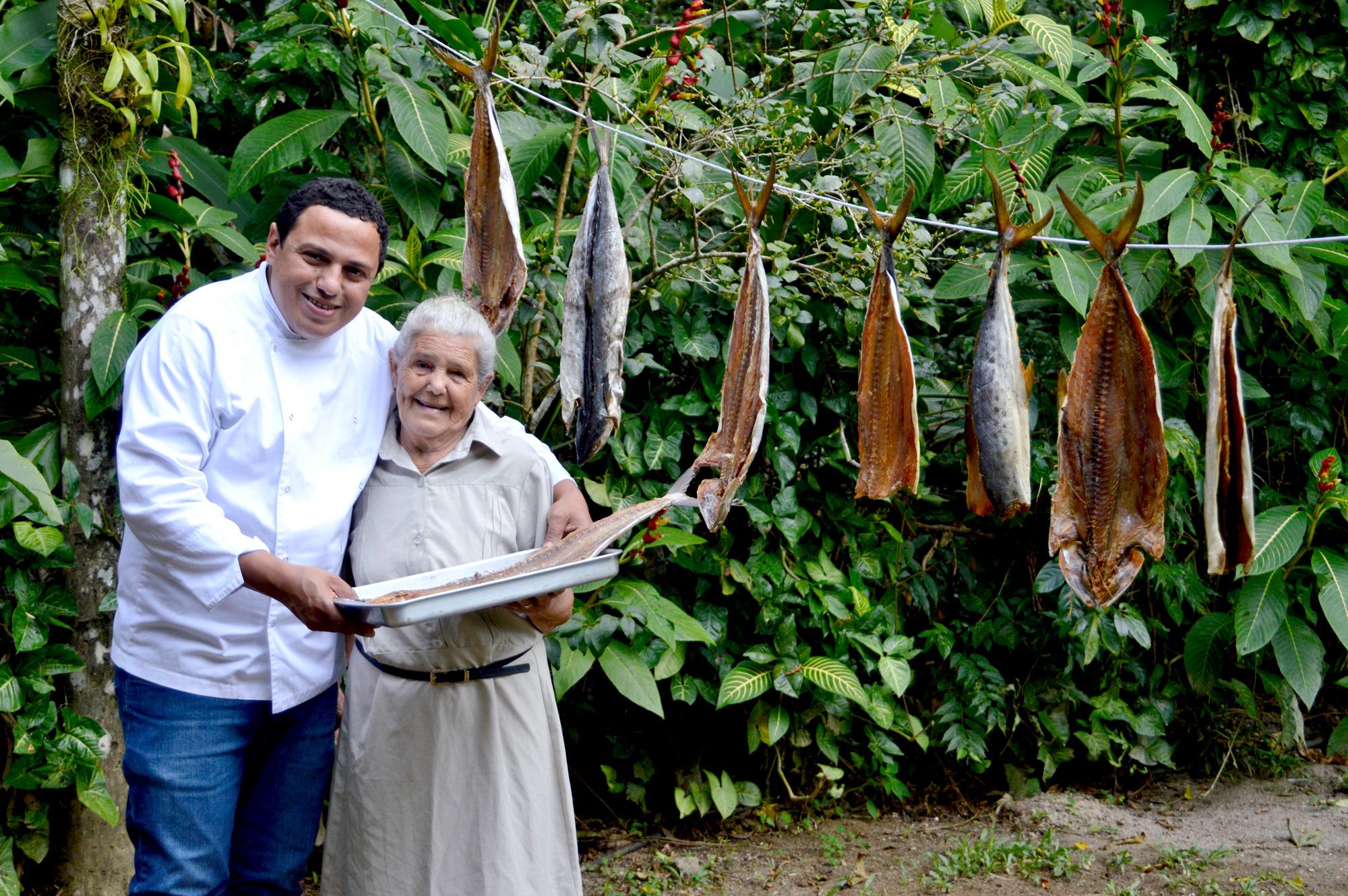 Chef Eudes e sua mãe, Madá, secando peixe no varal, técnica que preserva o pescado.