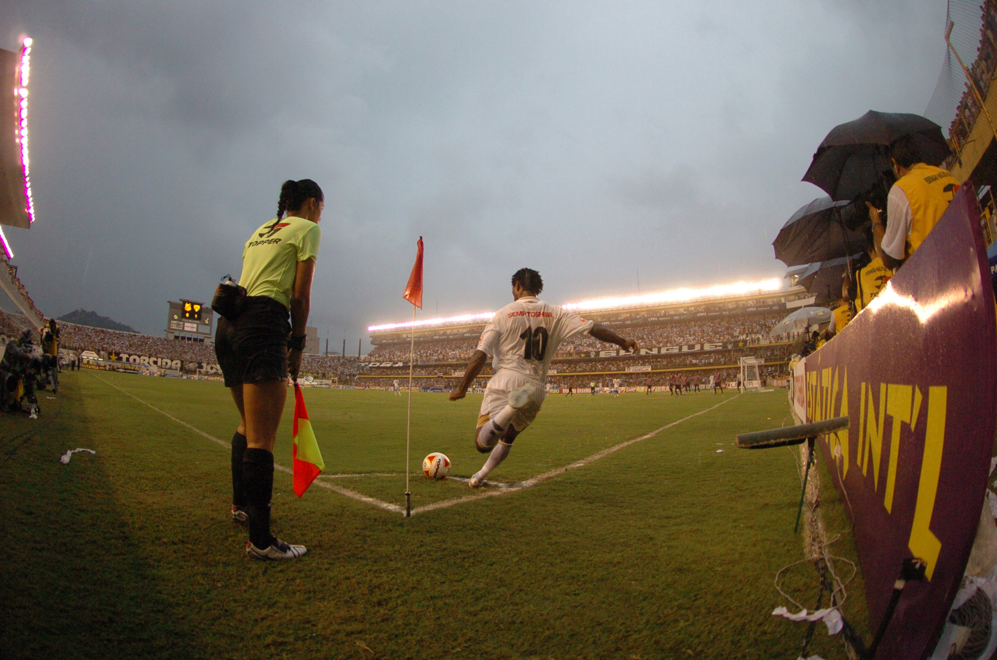 Zé Roberto, do Santos, batendo escanteio, ao lado da bandeirinha Ana Paula dos Santos Oliveira, durante jogo contra o São Paulo, pelo Campeonato Paulista de Futebol, no Estádio da Vila Belmiro.