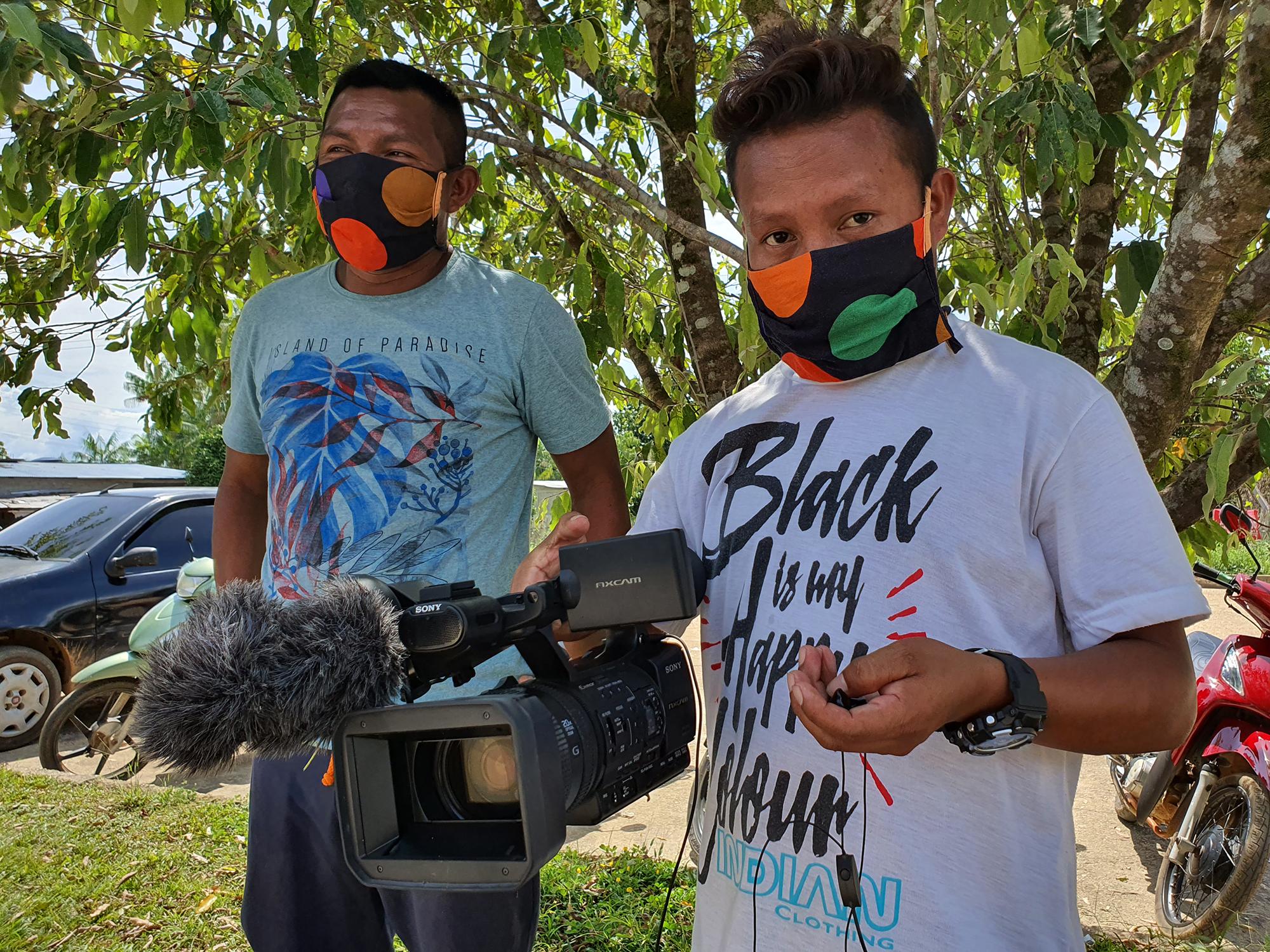 os comunicadores Álvaro Socot, do povo Hupdah, e Moisés Baniwa durante reportagens na rua em São Gabriel da Cachoeira
