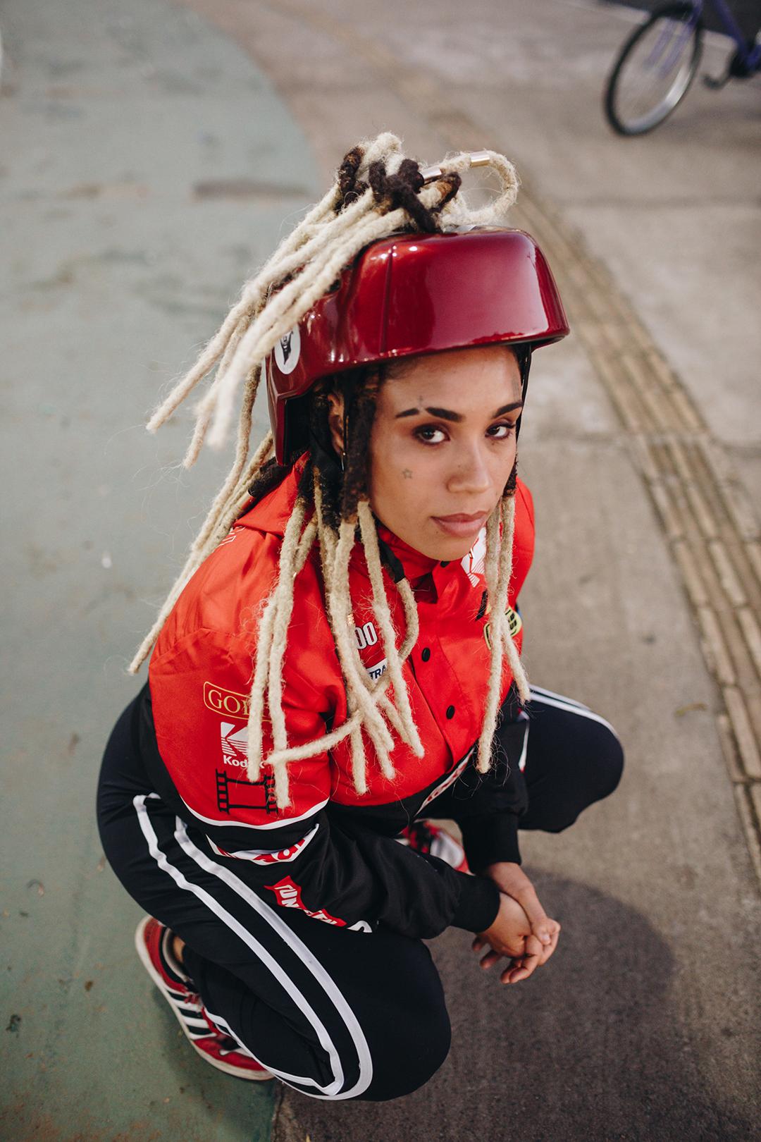 Lívia Suarez, co-fundadora da La Frida Bike com o capacete desenvolvido para pessoas crespas