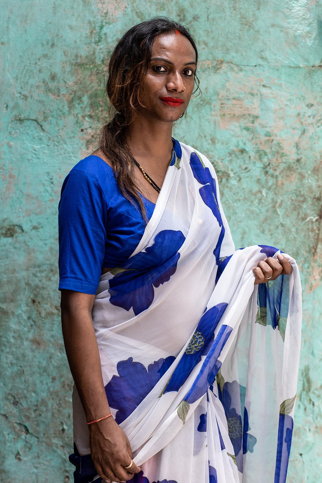 Rupaa posa para retrato na frente de uma casa em Varanasi. Durante uma conversa, ela relaciona sua identidade de gênero a decisões divinas